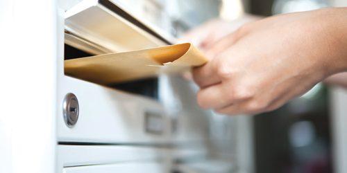 NOVA Woman putting envelope in mailbox e1492032923400