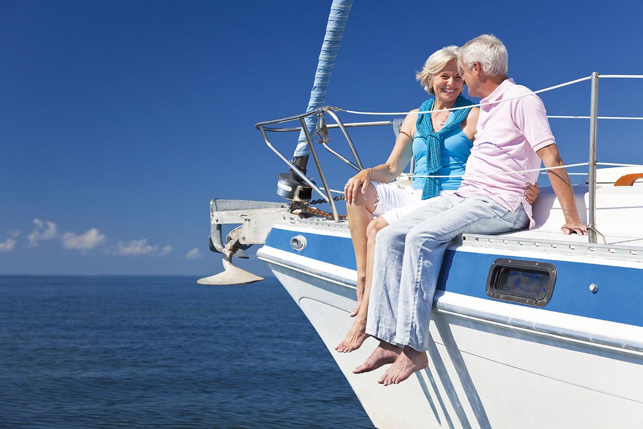 Happy Senior Couple Sitting on a Sail Boat