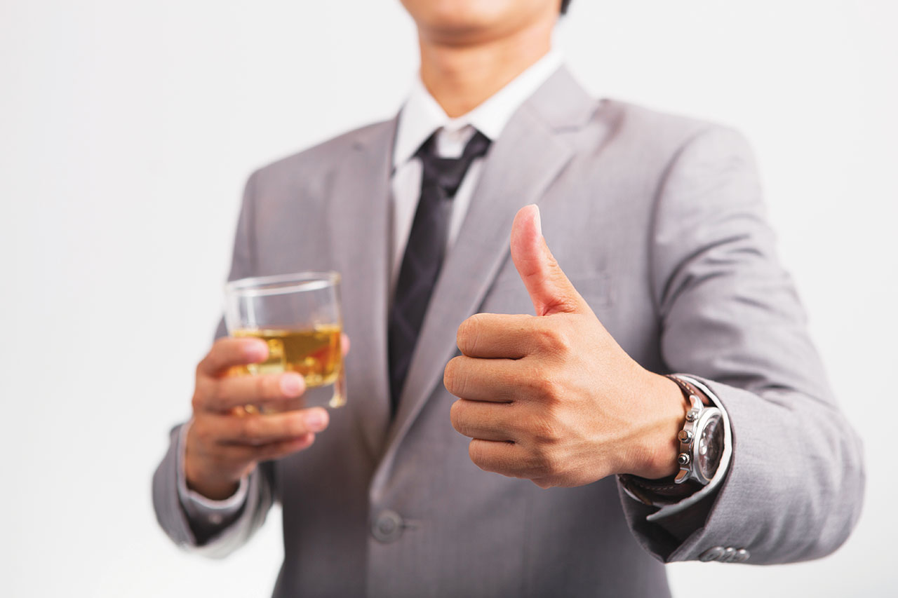 Two businessman in shirt and tie talking to each other while drinking whiskey after office hour